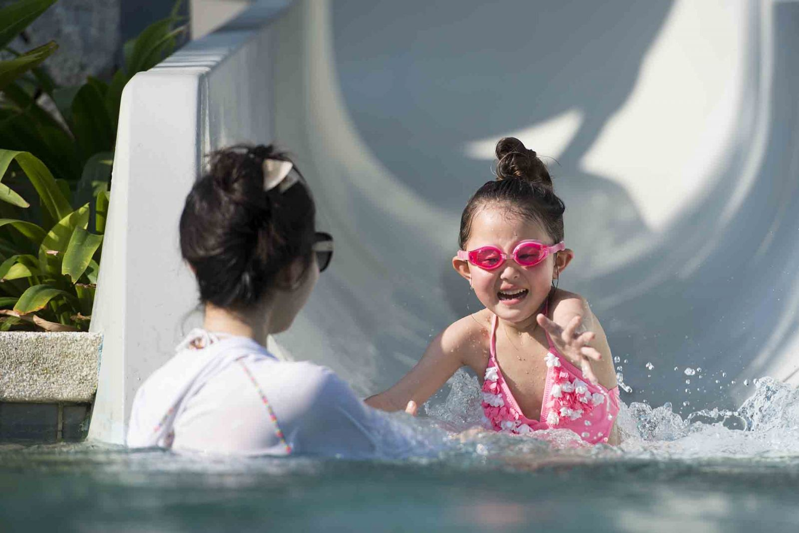 Babysitter catching girl at bottom of water slide