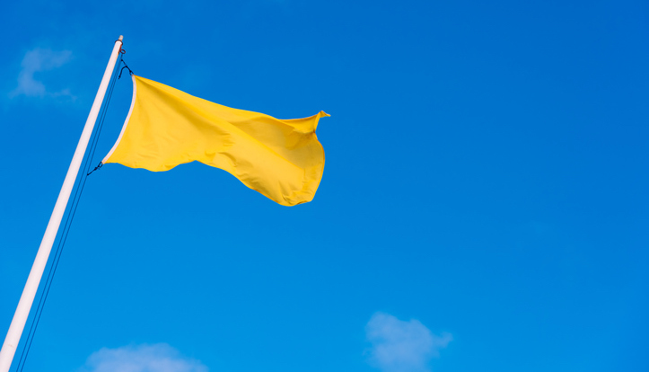 beach hazard flag in yellow with blue sky background