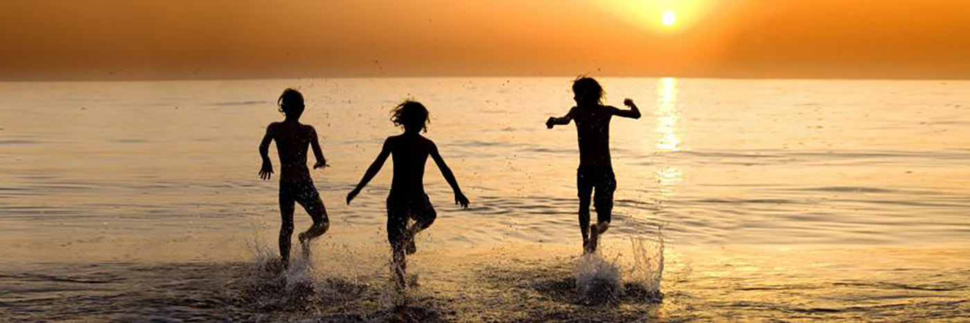 Kids jumping in the ocean at sunset