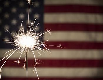 American flag with a sparkler in front