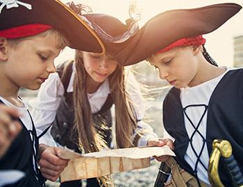 Kids dressed as pirates looking at a treasure map