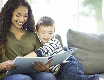 Babysitter with boy reading a book