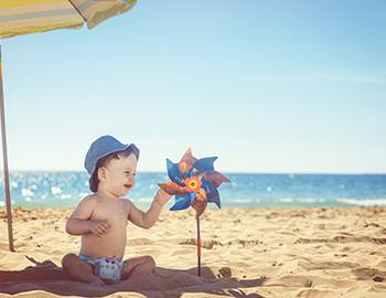 Baby at the beach playing with a windmill