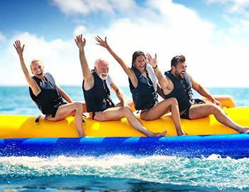 Family riding a banana boat in the water