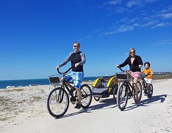 Family riding bikes on the beach