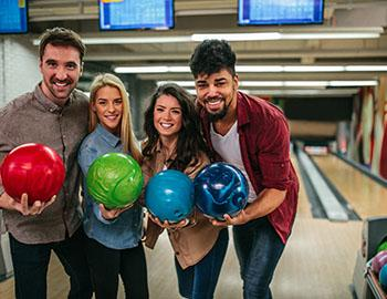 Friends living up with bowling balls at a bowling alley