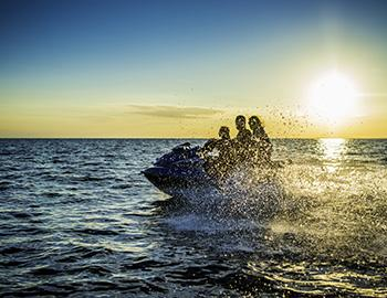 Family riding a jet ski at sunset
