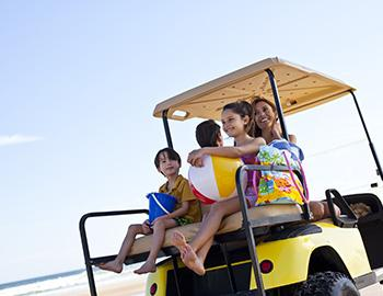 Family on a golf cart on the beach