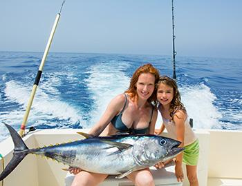 Mom and daughter holding catch on boat