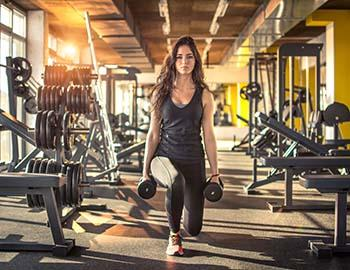 Woman squatting with weights at a gym