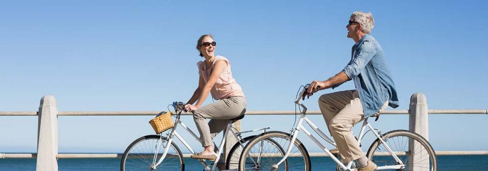Couple riding bikes by the bay