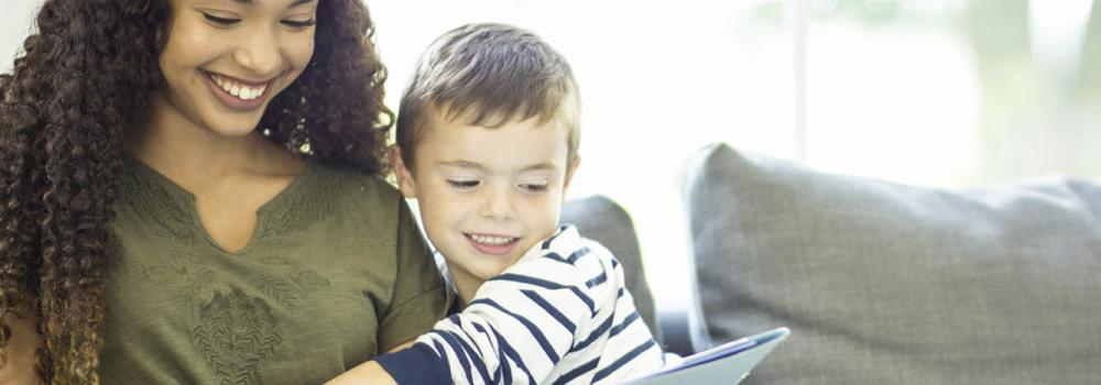 Woman reading a book to a boy she's babysitting