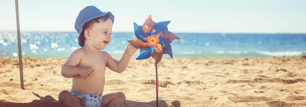 Baby on the beach playing with a windmill