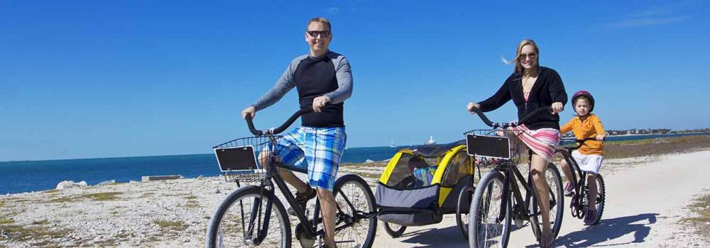 Family riding bikes on the beach together