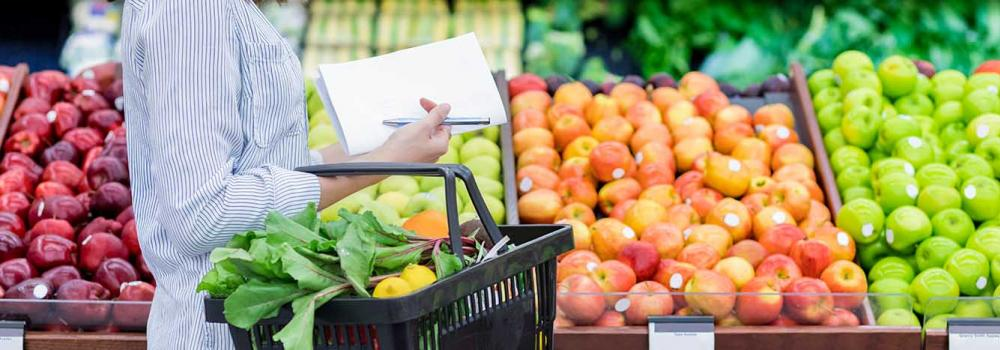 Woman grocery shopping at store with list