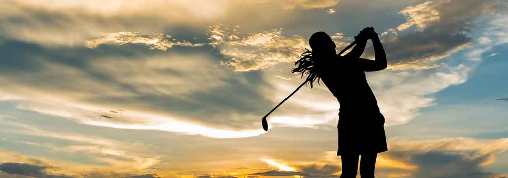 Silhouette of a female golfer at sunset