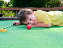 Kid eyeing golf ball on mini golf course