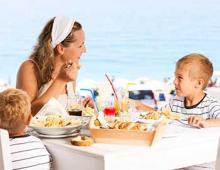 Mom and kids dining together at a beachfront restaurant